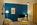 salon avec un mur bleu profond, un sol bois et du mobilier aux lignes scandinaves